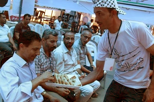 Palestinians distribute sweets to celebrate the kidnap of three Jewish teenagers
