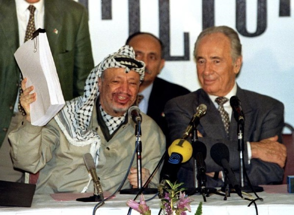 Yasser Arafat waves the second Oslo agreement as Shimon Peres looks on
