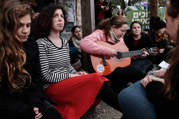 "A vigil for 23-year old Shlomit Krigman, murdered last month. The sticker on the guitar reads ""Rabbi Kahane was right!"""